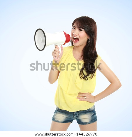 Young attractive  asian woman shouting with a megaphone - stock photo