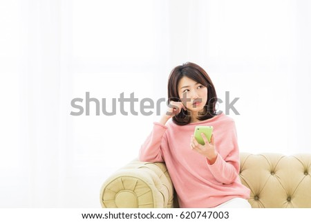 young attractive asian woman using smart phone, thinking