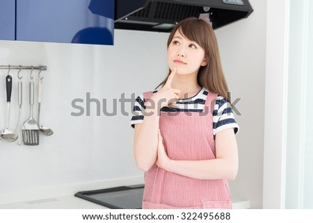young attractive asian woman who cooks and think - stock photo