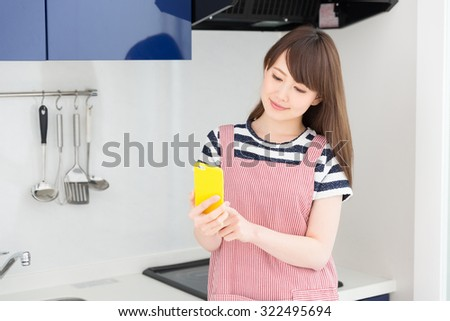 young attractive asian woman who cooks while watching a smart phone - stock photo