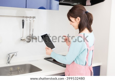 young attractive asian woman who cooks while watching tablet pc
