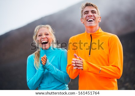 Young attractive athletic couple, wearing sporty clothes on trail - stock photo