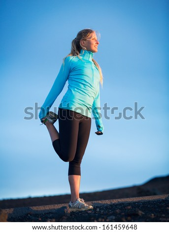 Young attractive athletic woman, wearing sporty cloths on trail, stretching before run