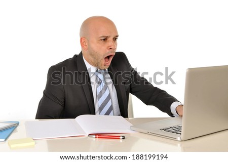 young attractive bald business man lsitting at office desk looking at computer reading and watching something thats makes him surprised , scared , leaving him in shock - stock photo