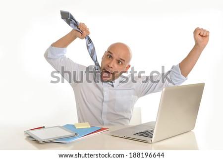 young attractive bald latin business man in stress , frustrated and desperate , going crazy working with computer at office desk - stock photo