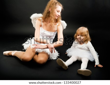Young attractive ballerina with 2 years old angel relaxing at black background