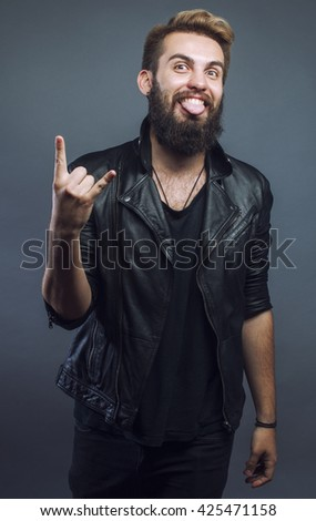 young attractive bearded hipster man gesturing emotional screaming in studio sucsess. fashion modern guy