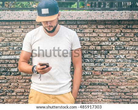 Young attractive Bearded man in gray T-shirt and Blue Baseball Cap holding modern Mobile Smartphone, texting sms