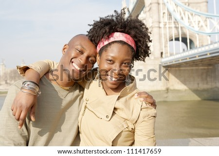 Young attractive black couple having fun while visiting the Tower of London and smiling.