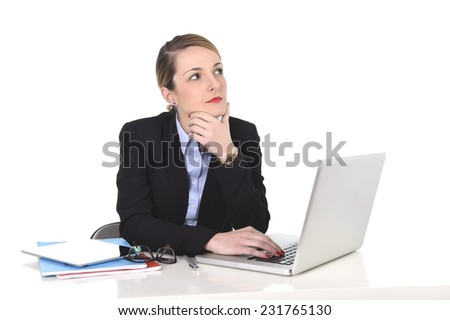 young attractive blond businesswoman thinking and looking thoughtful, pensive and using imagination distraught while working on computer laptop at office desk - stock photo