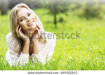 Young attractive blond girl is relaxing in the park laying on grass