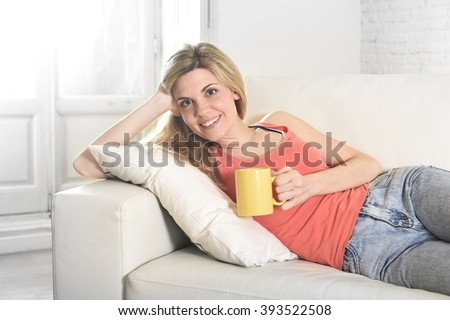 young attractive blond hair woman holding cup of coffee lying on sofa couch at home living room smiling happy and relaxed lifestyle concept - stock photo