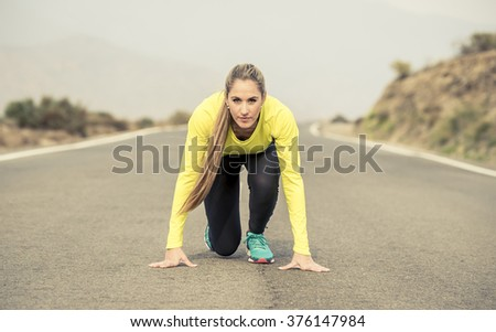 young attractive blond sport woman ready to start running practice training race starting on asphalt road mountain landscape looking at camera with determination in high performance and energy concept - stock photo