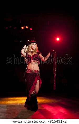 Young attractive blond woman circus artist  dancing with a whip and gipsy dress with funny hat