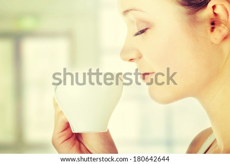 Young attractive blond woman drinking coffee in office - blured background - stock photo