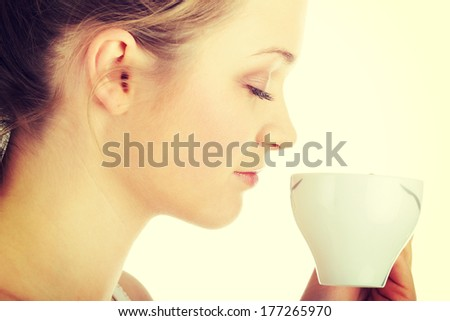 Young attractive blond woman drinking coffee, isolated on white background