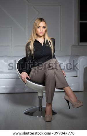 Young attractive blond woman wearing business clothes sitting on a chair - stock photo