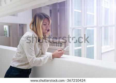 young attractive blonde business woman using a cellphone to check e-mail.beautiful female student typing a message on her smart-phone               - stock photo