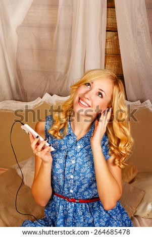 Young attractive blonde girl enjoying music with headphones, holding a tablet PC. Girl sitting on the bed in the bedroom. The concept of youth and technology. - stock photo