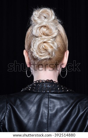 Young attractive blonde in a leather jacket. She is rebellious, she has a creative mohawk and heavy makeup. She wears a lot of metal accessories. Back of the head. - stock photo