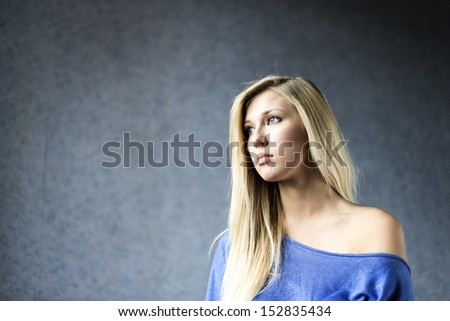 Young attractive blonde portrait. Blue background  - stock photo