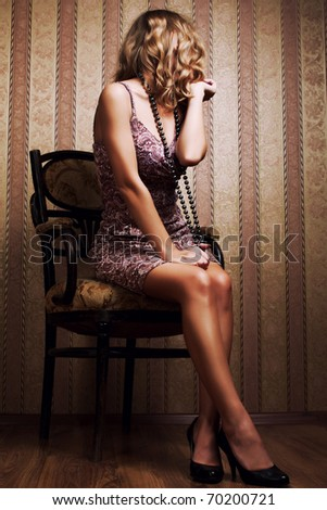 young attractive blonde poses in a luxurious interior