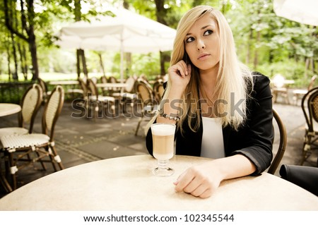 Young attractive blonde talking phone in the restarurant - stock photo