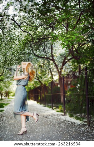 Young attractive blonde woman dancing on the road in the spring under the trees