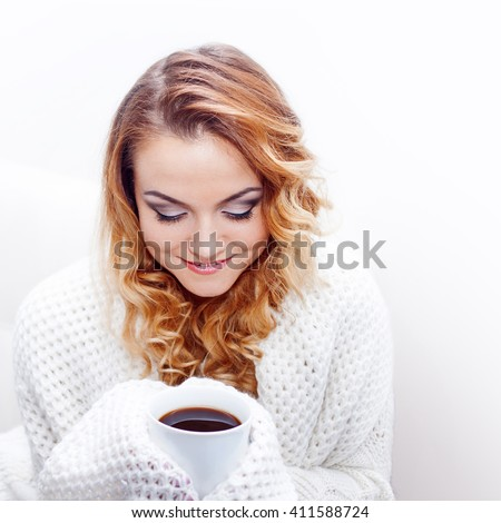 Young attractive blonde woman in a warm sweater drinking hot coffee,  white background, place for your text