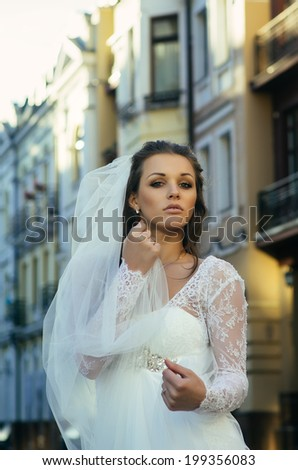 Young attractive bride posing on a street