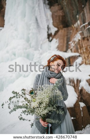 Young attractive bride with the bouquet over snowy background - stock photo