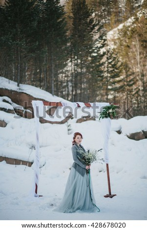 Young attractive bride with the bouquet over snowy nature background. Wedding arch - stock photo