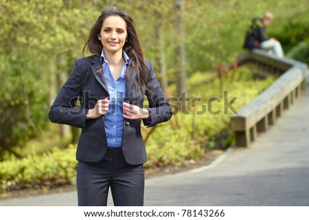 young attractive brunette businesswoman in park, wear blue shirt and grey suit, outdoor shoot