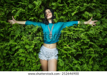 Young, attractive brunette lays back on the lush green foliage. Arms spread wide in the arms closed his eyes with a smile. Top view. - stock photo