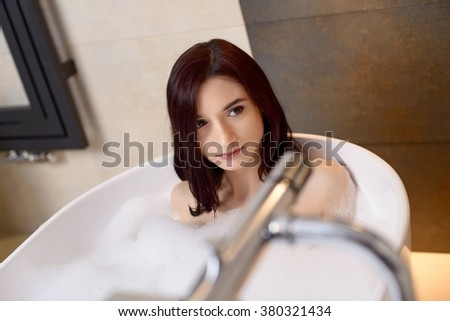 Young attractive brunette taking bath with foam. Relaxed. Woman in bathroom - stock photo