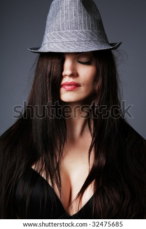 Young attractive brunette wearing black bra and gray hat.
