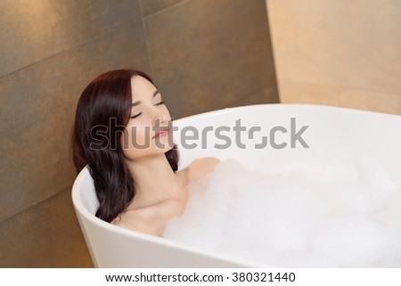 Young attractive brunette woman relaxing in bath with foam. Woman in bathroom - stock photo