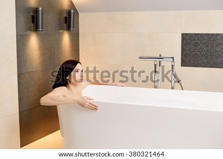 Young attractive brunette woman relaxing in bath. Woman in bathroom - stock photo