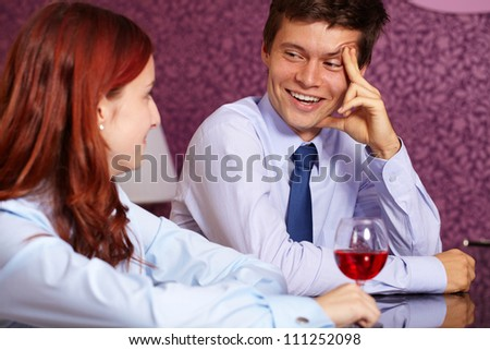 Young attractive business couple drink wine in restaurant - stock photo
