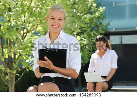 young attractive business ladies sitting on the street