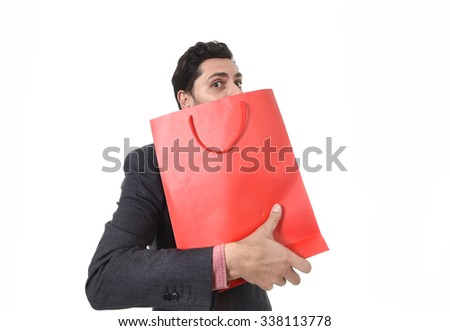 young attractive business man in stress holding shopping bag looking greedy after buying bargain isolated on white background - stock photo