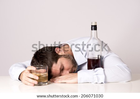 young attractive business man with beard  wearing blue shirt and tie drunk and drinking  Scotch or Whisky sleeping on office desk at work isolated on clear background  - stock photo