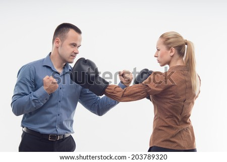 Young attractive business woman in boxing gloves attacking man with fists, isolated on white background