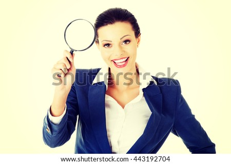 Young attractive business woman looking into a magnifying glass - stock photo