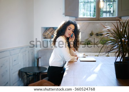 Young attractive business woman making a business call during the lunch break. beautiful girl working with a laptop in a cafe - stock photo