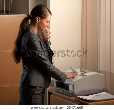 young attractive business woman sending fax - stock photo