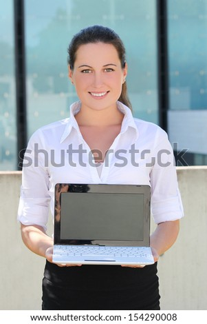 young attractive business woman showing laptop screen in the street
