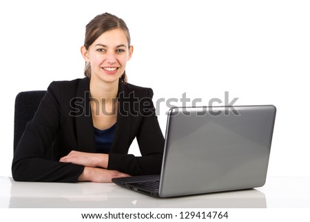 Young attractive business woman sitting behind a desk isolated on white