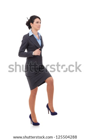Young attractive business woman stepping on imaginary step and looking away from the camera, upwards, suggesting progress - stock photo