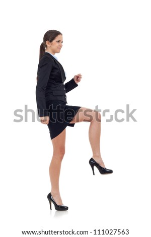Young attractive business woman stepping on imaginary step. Isolated on white.